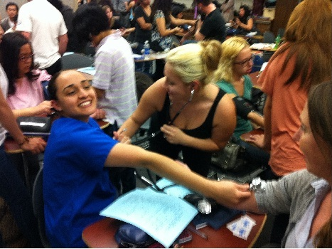 student enthusiastically offering arm to have blood pressure taken by other students