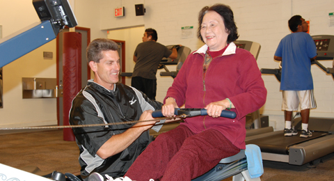 Doctor Sos helping an attendee with the rowing machine.