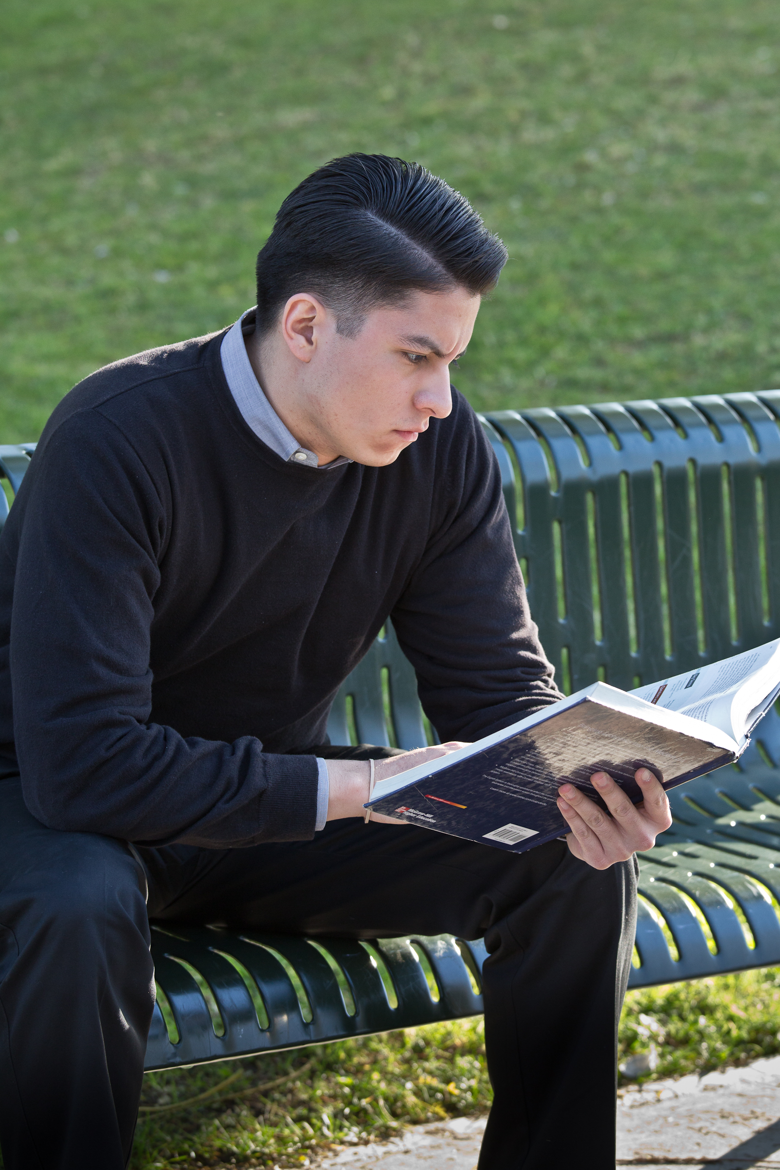Student Reading while sitting on a bench